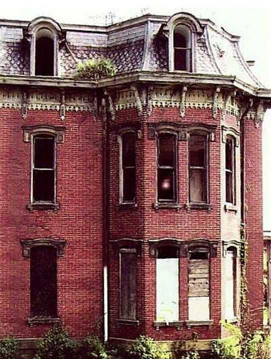 Фигура женщины в окне второго этажа, стоящая неподвижно...