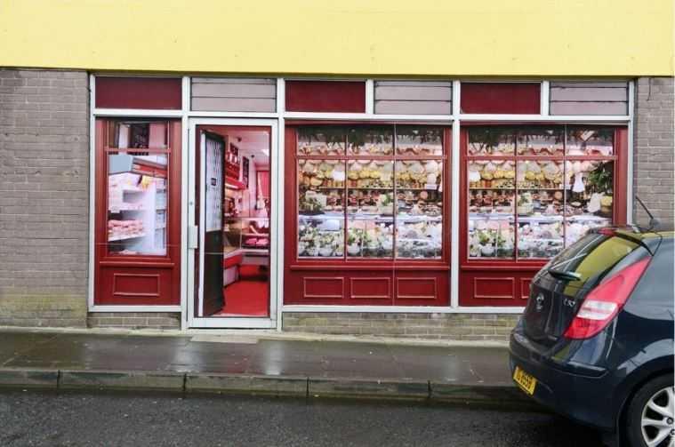 У некоторых пустых магазинов в деревне есть большие наклейки на окнах, чтобы они выглядели занятыми.