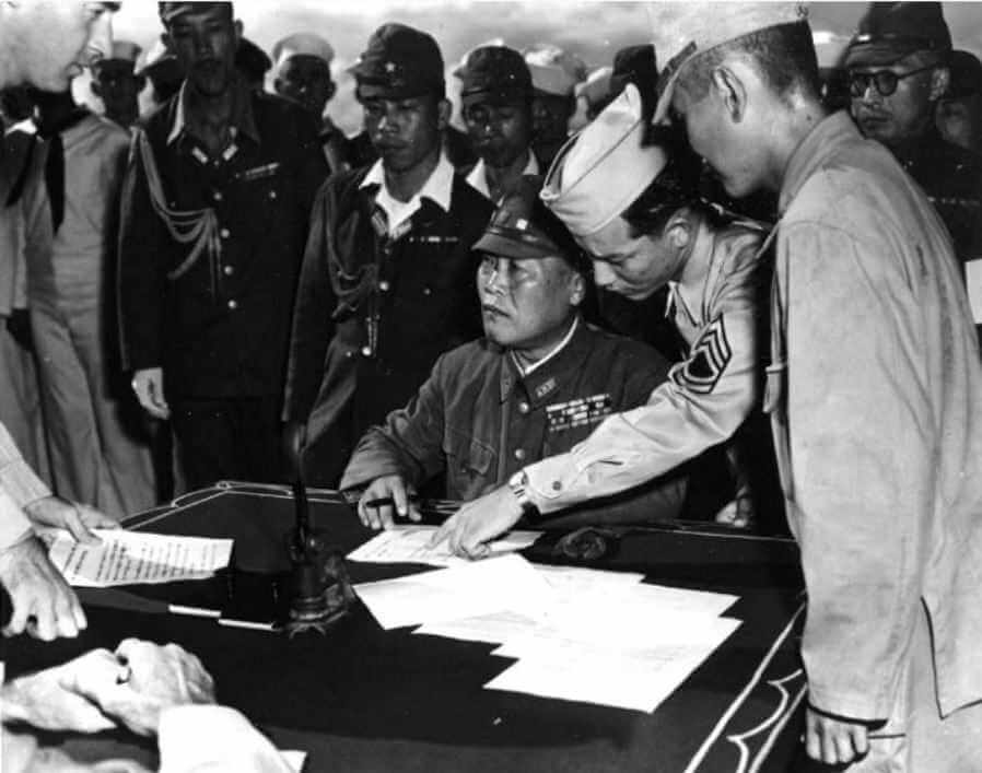 Генерал-лейтенант Татибана подписывает документы о капитуляции на острова Бонин, у побережья Чичидзима, 1945 г.