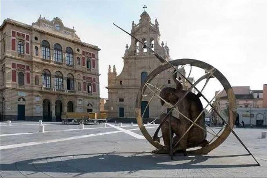 Монументальная, бронзовая статуя в центре шестиугольной площади на фоне коммуны и церкви. Город Граммикеле, Сицилия.